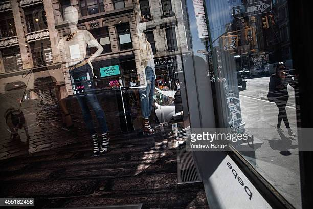 A woman walks past a window display near the construction site at 42 Crosby Street which is being developed into a luxury apartment building with 10...