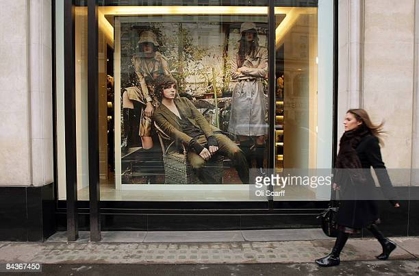 A woman walks past a window display of designer clothing retailer Burberry's flagship store in Knightsbridge on January 20 2009 in London England...