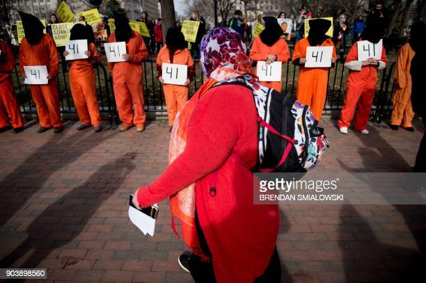 A woman walks past activists protesting the Guantanamo Bay detention camp during a rally in Lafayette Square outside the White House January 11 2018...