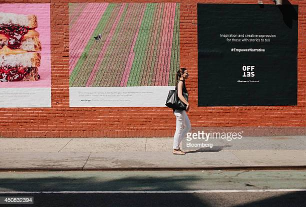 A woman walks past advertisements in the SoHo neighborhood of New York US on Wednesday June 18 2014 The Bloomberg Consumer Comfort Index a survey...