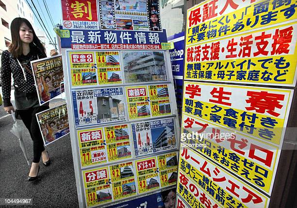 A woman walks past advertising billboards for rented apartments put up outside a real estate agent in Tokyo Japan on Saturday Sept 25 2010 'Reikin'...