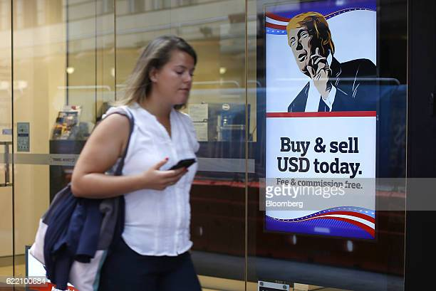 A woman walks past an advertisement featuring a cartoon of US Presidentelect Donald Trump at a currency exchange store in the central business...