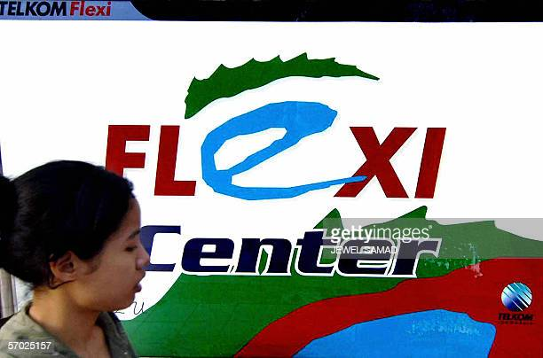 A woman walks past an advertisement for a mobile phone operator in Jakarta 09 February 2006 Three major telecommunication operators of Indonesian PT...