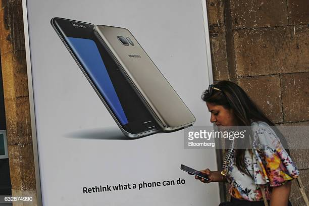 A woman walks past an advertisement for Samsung Electronics Co smartphones in Mumbai India on Friday Jan 27 2017 While economists urge more...