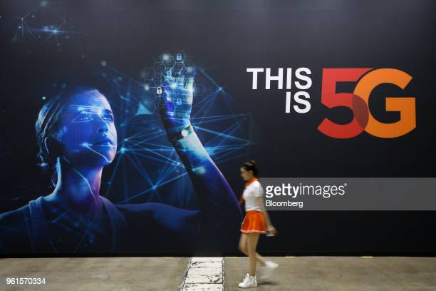 A woman walks past an advertisement for SK Telecom Co at the World IT Show 2018 in Seoul South Korea on Wednesday May 23 2018 The show runs through...