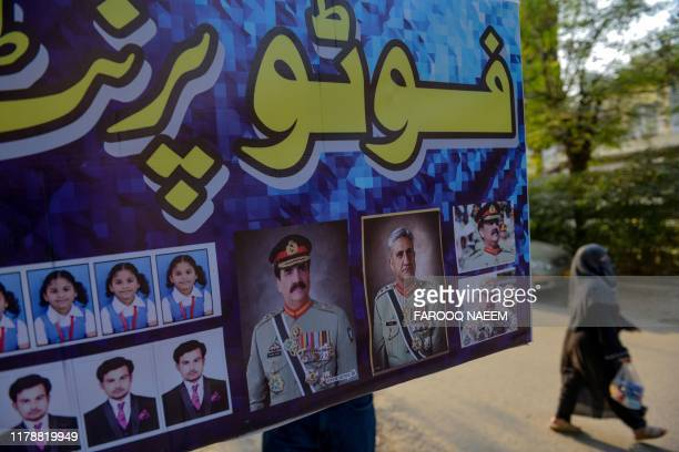 A woman walks past an advertisementshowing photos of former countryarmy chiefRaheel Sharif and current Army ChiefGeneralQamar Javed Bajwa...