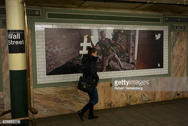 A woman walks past an advertising billboard for Twitter showing protagonists in a Middle Eastern conflict scene at the Wall Street subway station in...