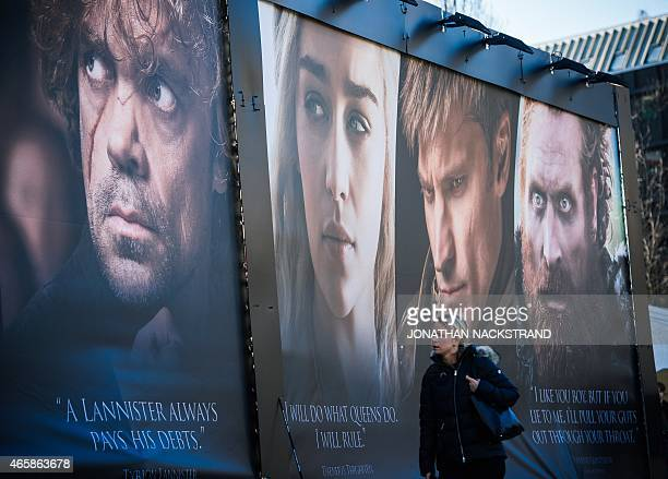 Woman walks past an advertising poster to promote the HBO American fantasy drama television series Game of Thrones outside the International Game of...