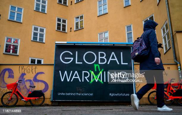 "Woman walks past an anonymous billboard with the headline ""Global Warming"" with the ""m"" crossed out to make it ""Global Warning"" urging people to..."