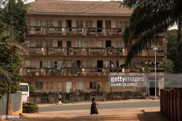 A woman walks past an apartment building in Bissau on Mardi Gras on February 13 2018 / AFP PHOTO / Xaume Olleros