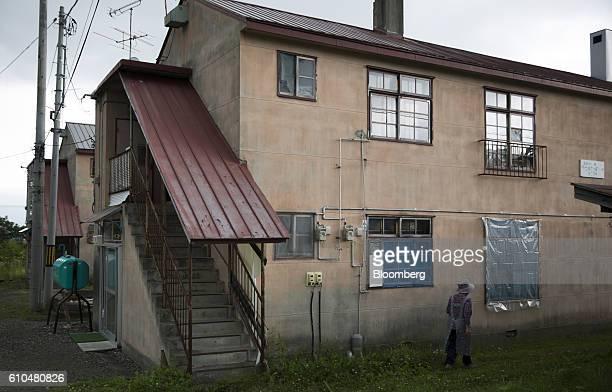 A woman walks past an apartment building in Yubari Hokkaido Japan on Thursday July 21 2016 Yubari a former coalmining town in northern Japan is...