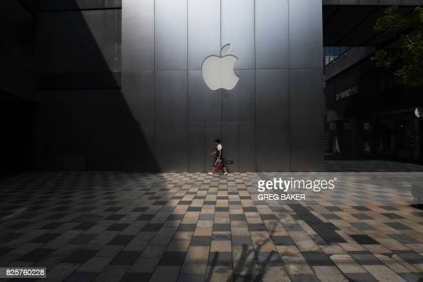 A woman walks past an Apple store in Beijing on August 3 2017 Apple has removed software allowing internet users to skirt China's 'Great Firewall'...