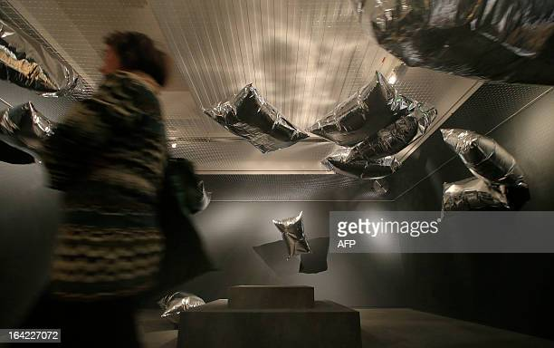 A woman walks past an artwork by US artist Andy Warhol with heliumfilled metalized plastic film hovering in a room titled 'Silver Clouds' and dated...