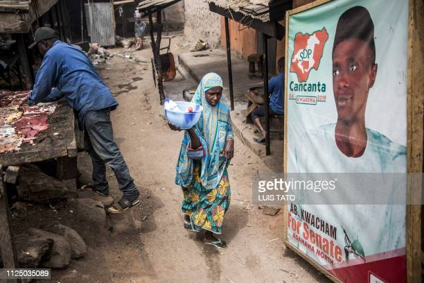 TOPSHOT A woman walks past an electoral poster at a market which was attacked last year by Boko Haram Islamists in the Nigerian city of Mubi Adamawa...