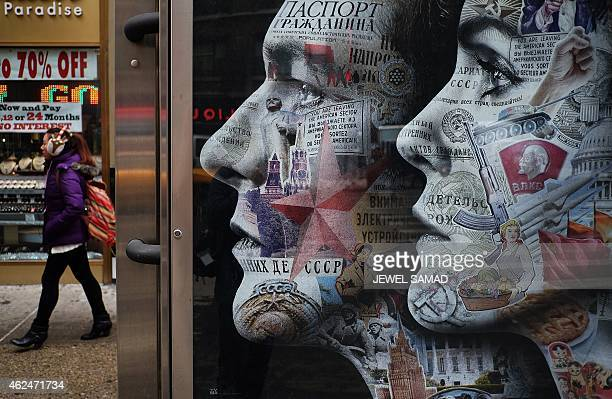 A woman walks past an electric billboard advertising television show 'The Americans' in New York's Times Square on January 29 2015 The show a...
