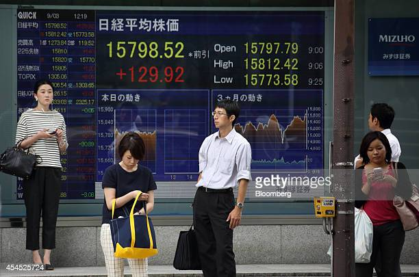 A woman walks past an electronic stock board displaying the midday figure top center of the Nikkei 225 Stock Average outside a securities firm in...