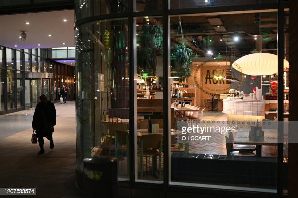 A woman walks past an empty Italian restaurant in central Manchester on March 17 as Britain's Chancellor of the Exchequer unveils a £330 billion...