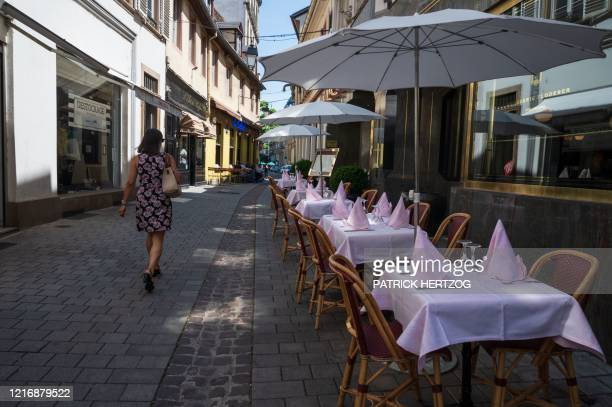 Woman walks past an empty restaurant's terrace in Strasbourg, eastern France, on June 2 as cafes and restaurants reopen in France, while the country...