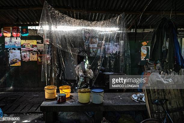 Woman walks past an empty stall at the Banjul market on December 3, 2016. / AFP / MARCO LONGARI