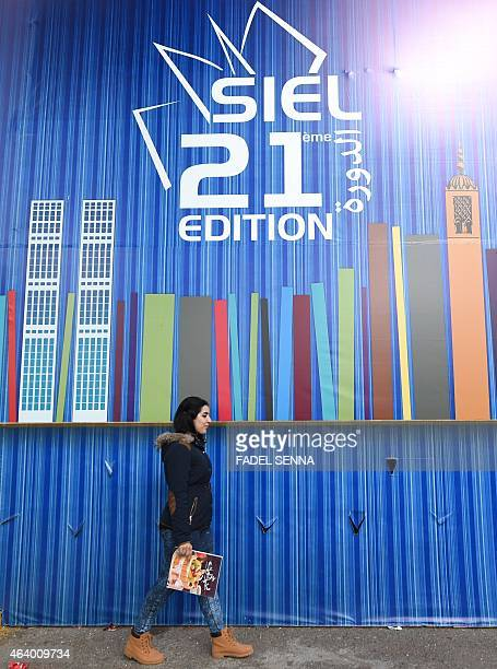 A woman walks past an exhibition placard on February 20 2015 during the 21st edition of the International Exhibition Of Publishing and Book Fair in...