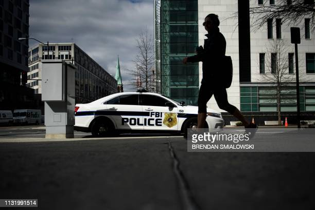 A woman walks past an FBI Police car near one of the office buildings used by independent prosecutor and former FBI director Robert Mueller on March...