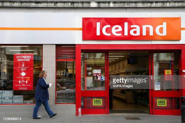 Woman walks past an Iceland supermarket in London.