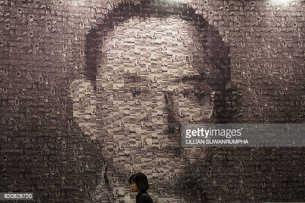 TOPSHOT A woman walks past an image of the late Thai King Bhumibol Adulyadej composited of photographs by members of the Royal Photographic Society...