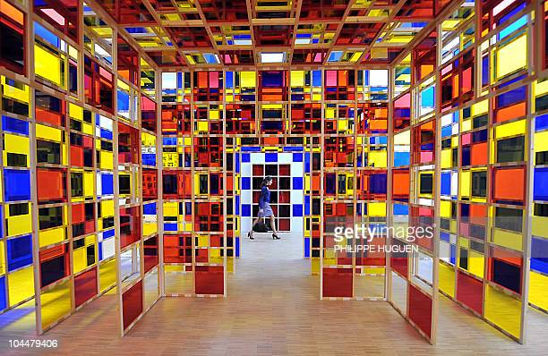 A woman walks past an installation by French artist Daniel Buren Les trois cabanes eclatees at the Lille Metropole museum of modern art on September...