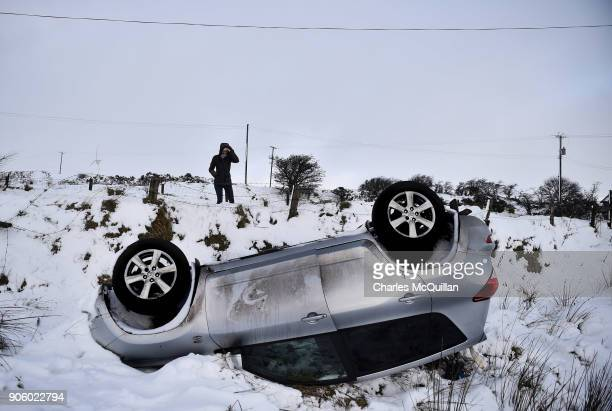 A woman walks past an overturned car on January 17 2018 in Belfast Northern Ireland The Met Office has placed an amber weather warning alert on the...