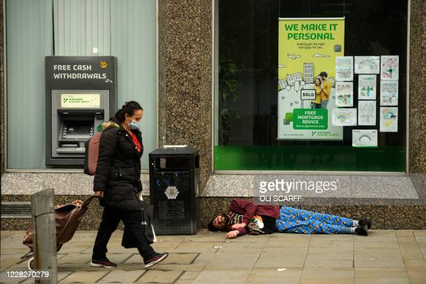 A woman walks past an unconscious man lying on the floor outside a bank in Manchester on August 30 2020