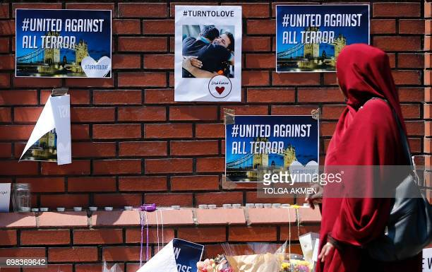 A woman walks past antihate posters and tributes outside Finsbury Park Mosque near to the scene of the June 19 van attack on pedestrians in the...