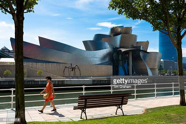 Woman walks past Architect Frank Gehry's Guggenheim Museum across River Nervion at Bilbao Basque country Spain