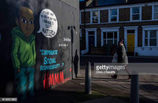 A woman walks past artwork by graffiti artist 'The Artful Dodger' on a wall in Brixton in response to an advert by clothing store HM which depicted a...