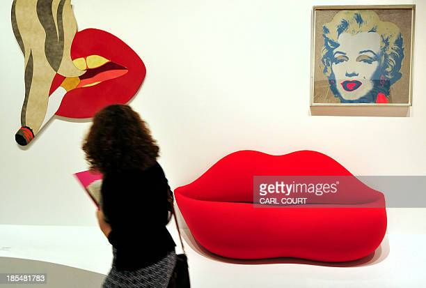 A woman walks past artworks titled 'Smoker Banner' by US artist Tom Wesselmann 'Bocca' by Studio 65 and 'Marilyn Monroe' by US artist Andy Warhol...