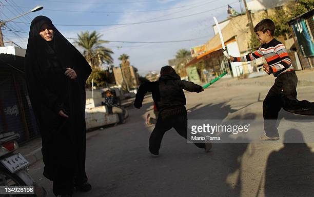 Woman walks past as children play while re-enacting the Battle of Karbala outside Seid Idrees mosque on the day before the festival Ashura on...