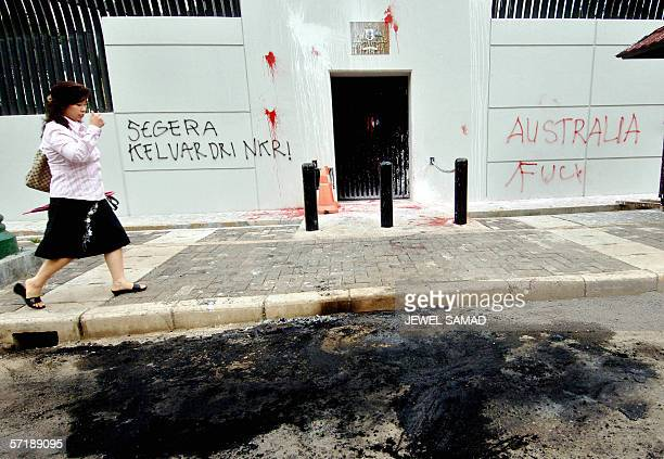 A woman walks past Australian embassy's wall with grafitti in Jakarta 27 March 2006 after a student demonstration Australia's envoy to Jakarta Bill...
