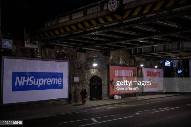 A woman walks past billboards adverts relating to the coronavirus pandemic at night time in Shoreditch on May 9 2020 in London England The UK is...