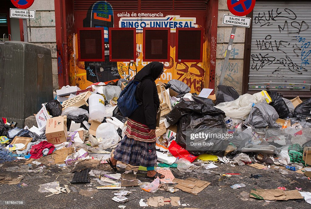 A woman walks past bins overflowing with rubbish in the city centre on November 13, 2013 in Madrid, Spain. Street cleaners, garbage collectors and public park gardeners working for Madrid city council started an indefinite strike 9 days ago after the private contracters plan to axe more than 1,000 jobs and introduce a 40% pay cut for the remaining workers.