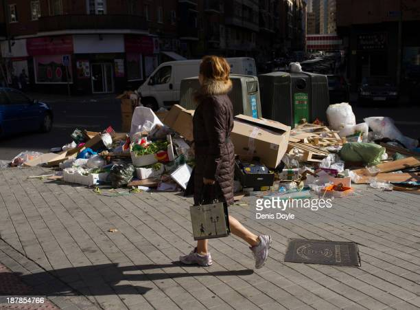 A woman walks past bins overflowing with rubbish in the city centre on November 13 2013 in Madrid Spain Street cleaners garbage collectors and public...