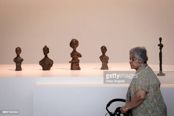 A woman walks past bronze busts at a retrospective exhibition of work by Swiss sculptor and artist Alberto Giacometti at the Guggenheim Museum June 7...