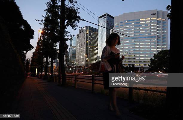 A woman walks past buildings at dusk in Tokyo Japan on Monday July 28 2014 Japan's June unemployment rate climbed 02 percent to 37 percent compared...