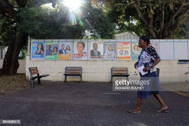A woman walks past campaign posters as she arrives to a polling station in La Possession on the French Indian Ocean island of La Reunion during the...