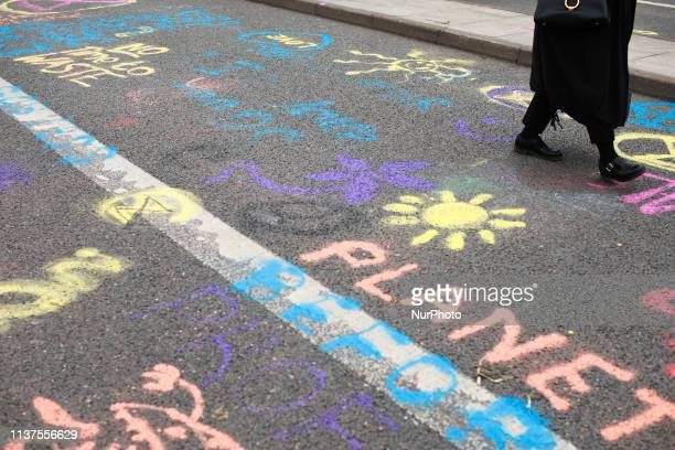 A woman walks past chalk messages written by members and supporters of climate change activist group Extinction Rebellion on Waterloo Bridge in...