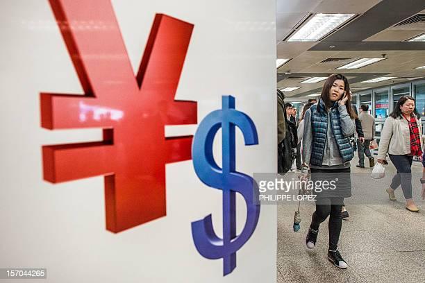 Woman walks past Chinese yuan and US dollars symbols in Hong Kong on November 28, 2012. The US Treasury on November 27 again stopped short of...