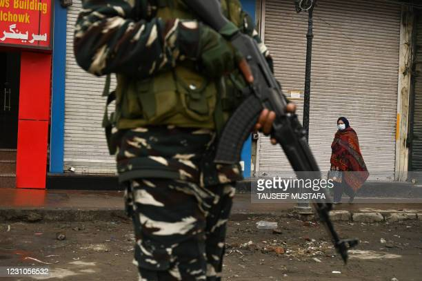 Woman walks past closed shops and an Indian government soldier standing guard during a one-day strike on the death anniversary of Afzal Guru, who was...
