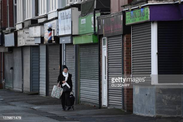 Woman walks past closed-down shuttered shops in Hull, in north-east England on November 30, 2020. - Hull will return to the England's highest...