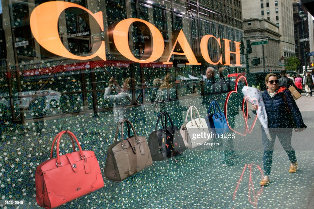 99f362f395c1 A woman walks past Coach bags in a window of Macy s flagship store ...