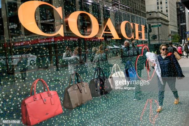 Woman walks past Coach bags in a window of Macy's flagship store, May 12, 2017 in the Herald Square neighborhood in New York City. The U.S. Commerce...