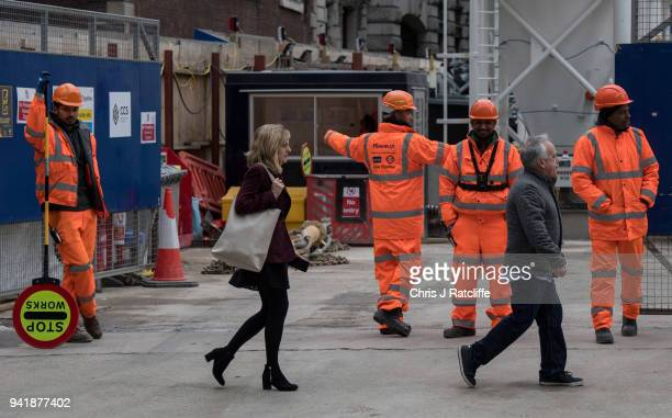 A woman walks past construction workers as the deadline nears for companies to report their gender pay gap on April 4 2018 in London England The...