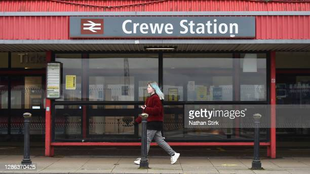 Woman walks past Crewe Train Station on November 18, 2020 in Crewe, Cheshire. The United Kingdom will continue to impose lockdown measures until...